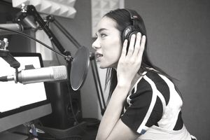 Female sitting at mic during a podcasting
