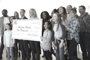 Enthusiastic community posing with large donation check