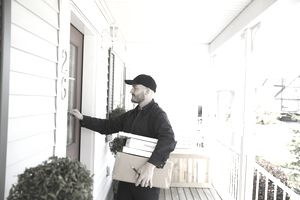 Delivery man with packages knocking at front door