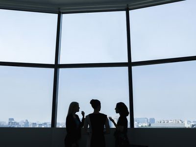 Silhouettes of three businesswoman in a high-rise office with a city view in the background.