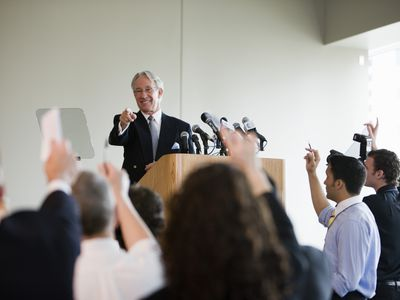 an older man answering questions at a press conference