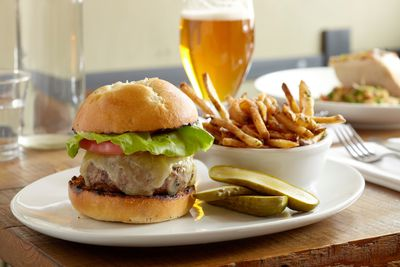 Burger, fries, and pickles with a beer on a restaurant table