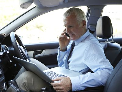 Businessperson working from front seat of car during travel