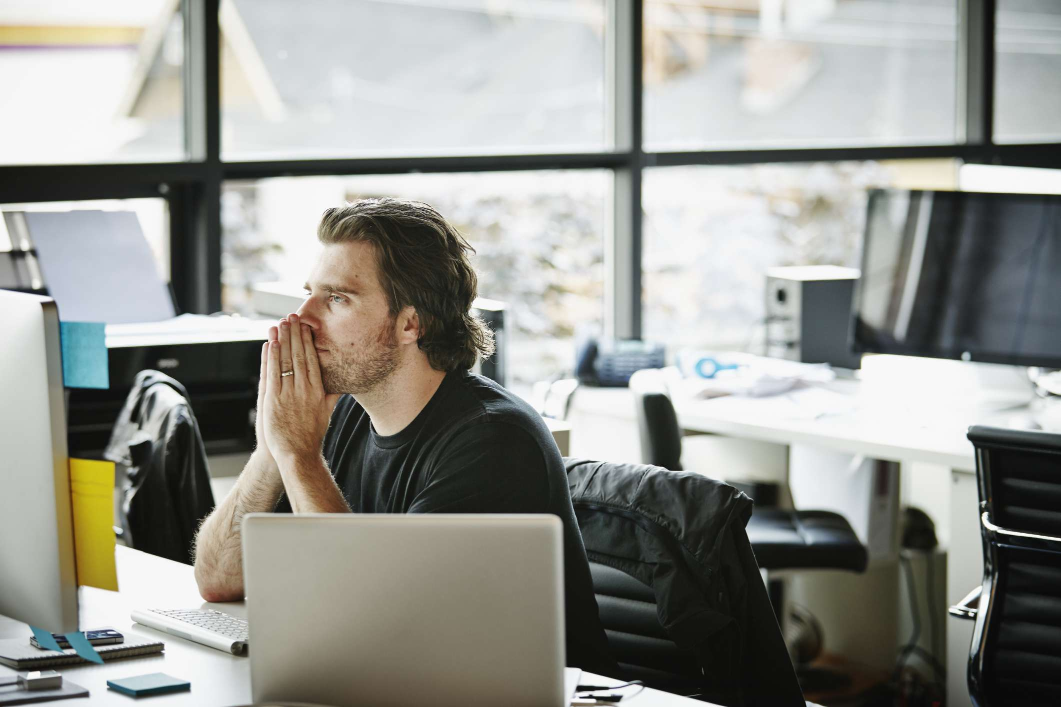 Man sitting at computer with hands on head