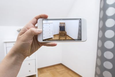 mobile phone displaying a chair in a room through augmented reality