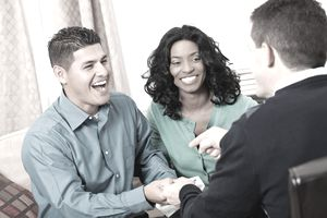 Couple on sofa smiling and shaking hands with a businessman