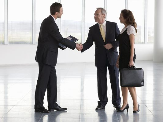 Business man shaking hands with real estate agent in commercial space