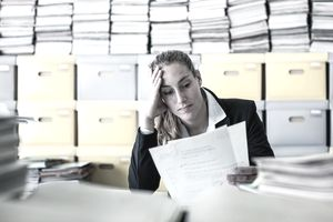 Frustrated woman in front of stacks of files