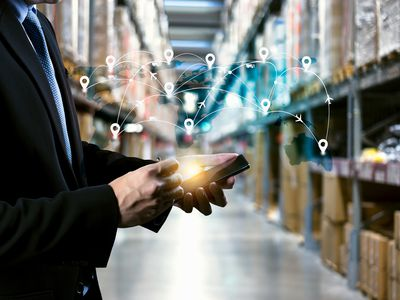 Warehouse manager holding tablet with AR application for check order pick time