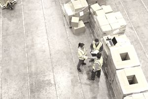 freight forwarder workers standing next to freight in boxes