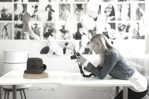 Woman taking picture of hat.
