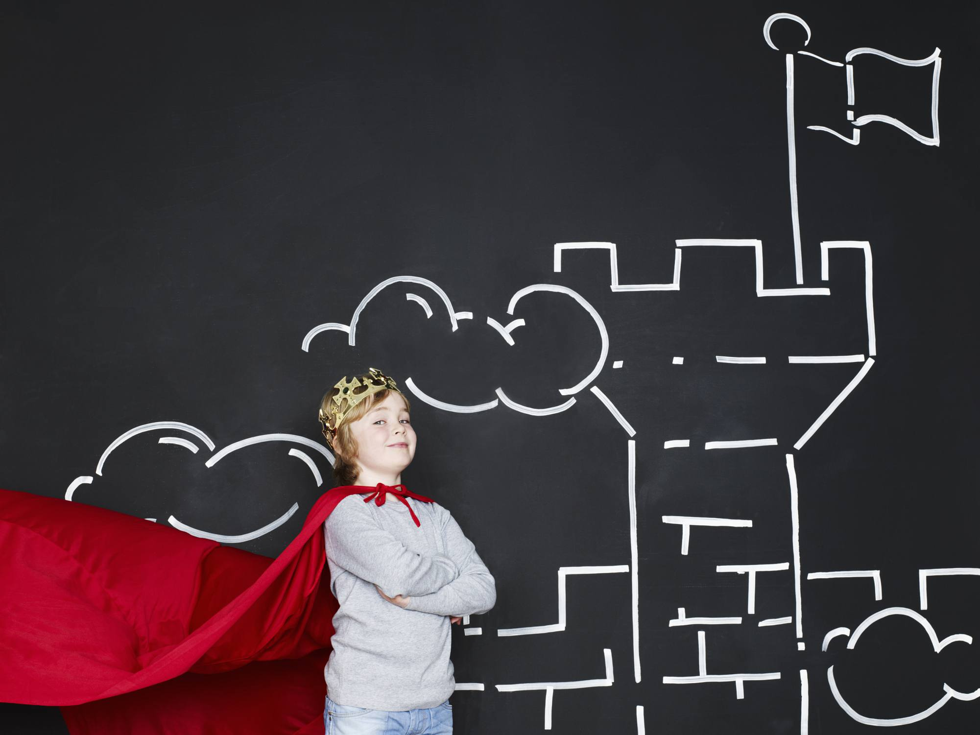 Boy in cape, like a superhero, standing in front of black board with drawing of castle on it