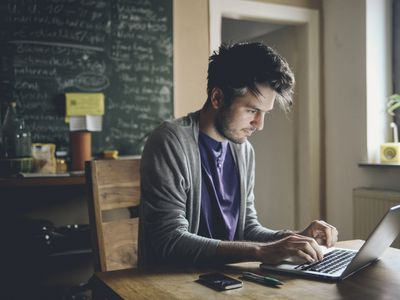 Man typing freelance work on a computer