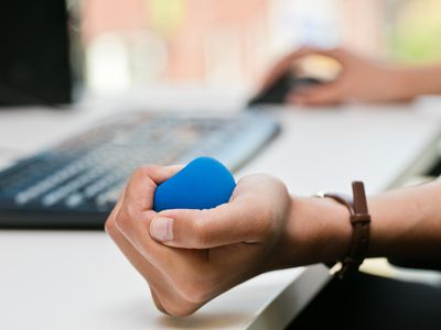 Hand squeezing stress ball next to computer keyboard