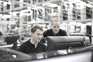 Employees using computer in logistics warehouse