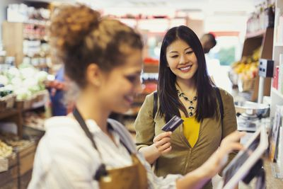 Smiling female shopper with credit card paying cashier at grocery store cash register