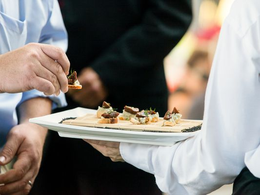 A server at catered event with tray of appetizers