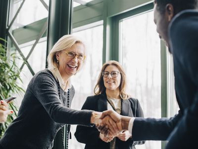Businesswoman shaking hands with a colleague while another one looks on