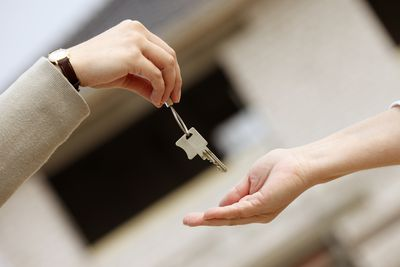 one person handing a house key to another person
