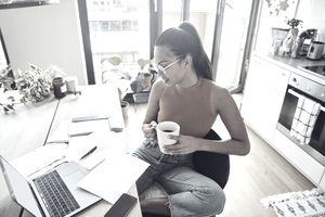Woman at her home, holds coffee cup and finishing paperwork