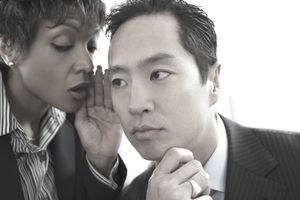 Businesswoman telling secret to businessman