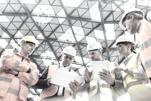 Foreman and construction workers using digital tablets in meeting at construction site
