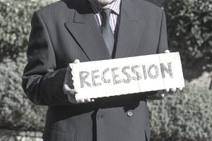 "Closeup of a man in a suit holding a piece of cardboard that says ""recession"""