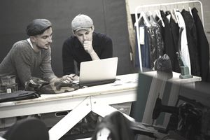 Two young clothing designers go over some info on a laptop screen.