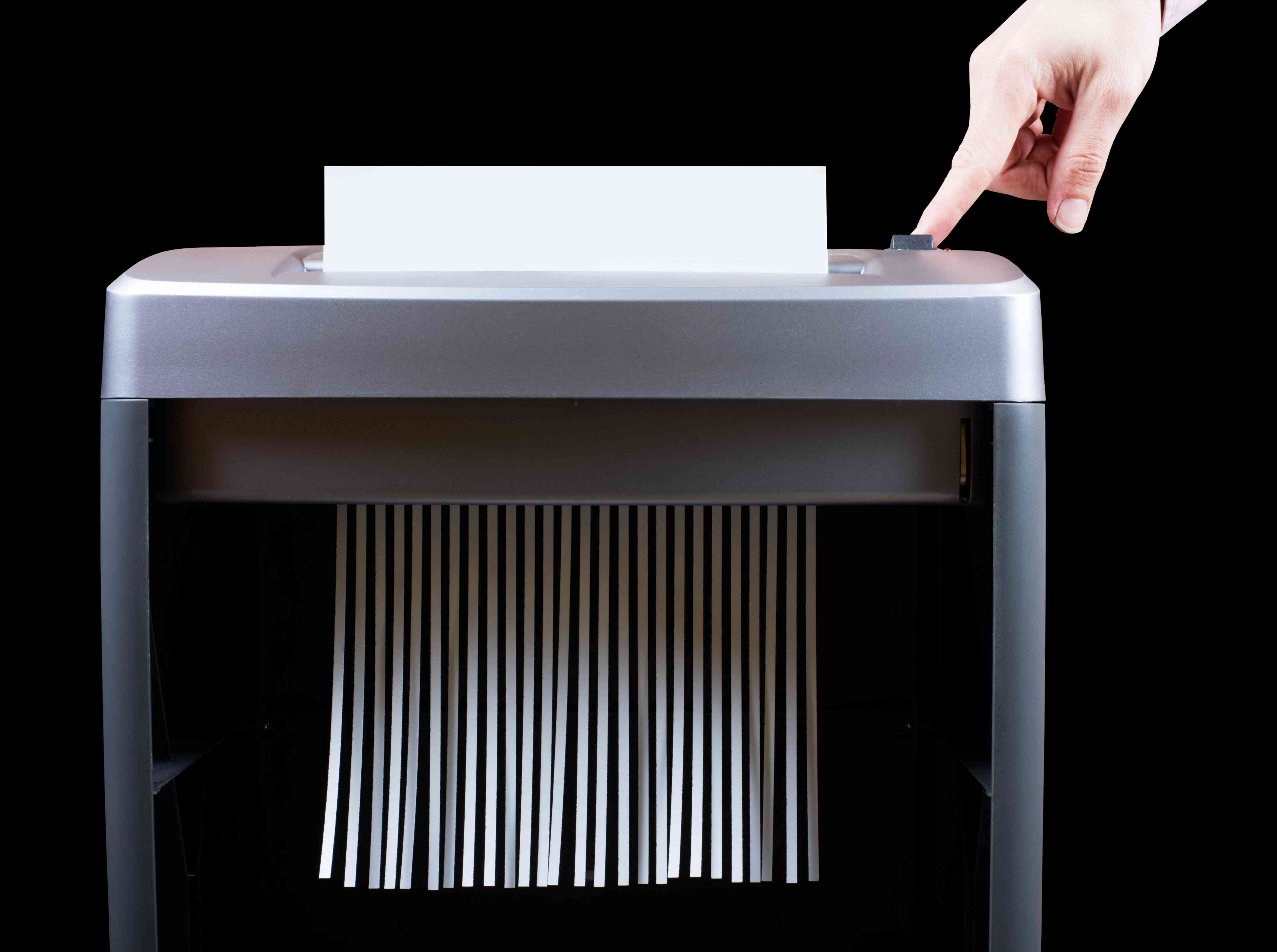 Closeup of a shredder with a hand pushing its button
