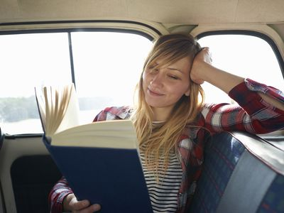 Woman reading a book in the back of a car