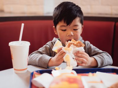 A Chinese boy have a lunch in a fast food shop