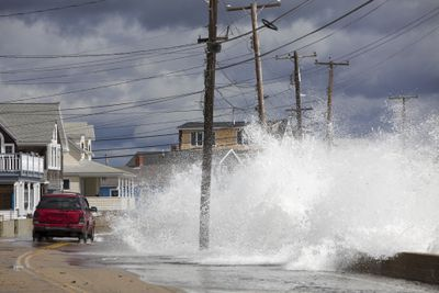Waves crashing against a break wall in conjunction with high tide and a storm as a red car drives on the road