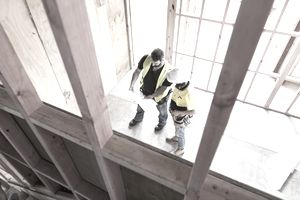 construction workers on a job site looking over paperwork