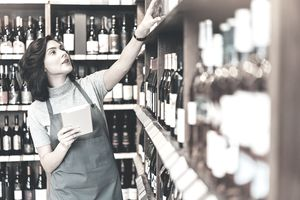 Busy young woman in the wine shop