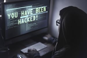 "Woman at computer with ""you have been hacked"" on the screen"