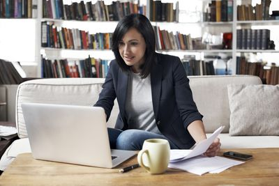 Woman sitting on couch using a laptopp