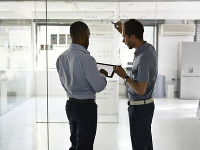 Businessmen holding digital tablet and writing strategy on glass wall