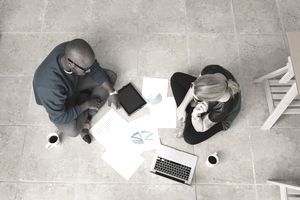 Man and woman sitting on floor of home doing work while drinking coffee