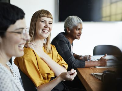 Smiling entrepreneur with female coworker looking away in meeting at workplace