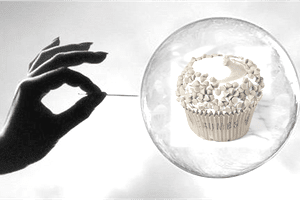 a person holding a pin to a bubble with a cupcake inside it