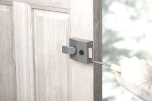 Person securing lock on door with screwdriver