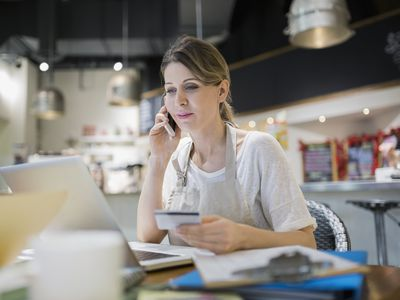 Small business owner building credit at laptop in cafe