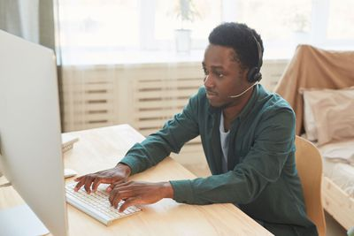 Young man in green long-sleeved shirt wearing phone headset typing on a computer in his bedroom.