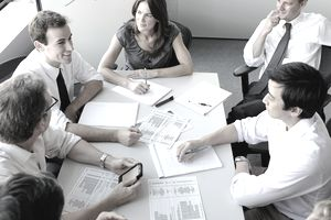 Professionals meeting in a business setting looking over finance paperwork.