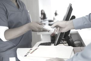 A nurse in blue hospital scrubs accepts an insurance card from a man in a blue oxford shirt.