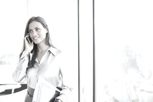 Businesswoman talking on cell phone in office