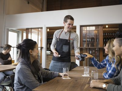 Women paying a waiter at a Canadian restaurant