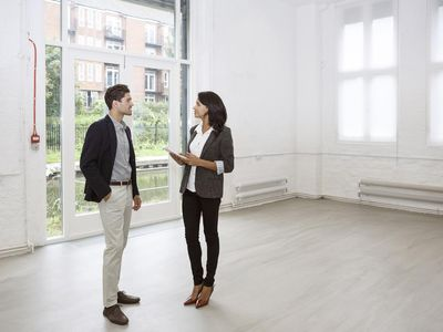 Young professional visiting a rental loft space with a commercial leasing agent.