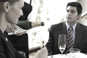 Waiter serving champagne to couple at restaurant.