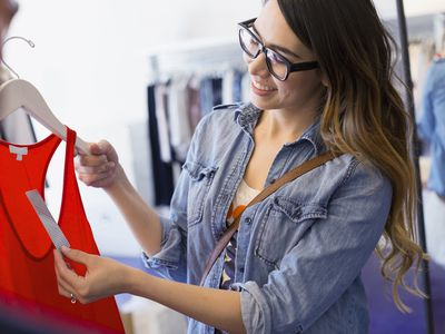 Woman looking at a price tag on a tank top